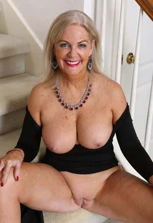 Classy mature Judy Mayflower shows big breasts  spreads naked on the stairs