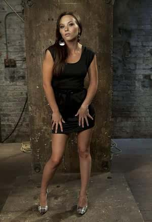 Solo girl peels off her black dress and underthings in a desolate basement